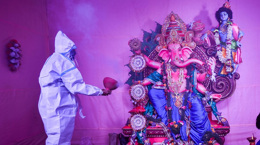 A devotee wearing a PPE kit offers prayers at a community puja pandal on the occasion of Ganesh Chaturthi, in Calcutta on Saturday.