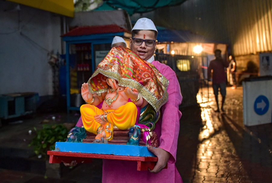 A devotee carries a Ganesh idol on the eve of Ganpati festival, at Dadar in Mumbai on Friday.