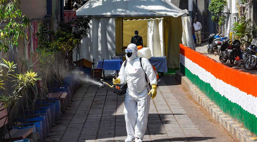 A health worker sanitises an area near Nizamuddin mosque after people attended the religious congregation at Tablighi Jamaat in New Delhi