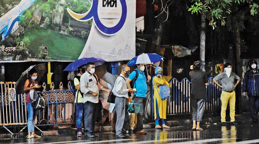 People wait for buses at the Park Street crossing in rain around 6.30pm on Sunday.