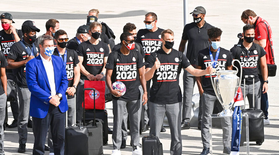 Bavaria Governor Markus Soeder, left, stands with the FC Bayern Munich team after their arrival at Munich Airport on Monday.