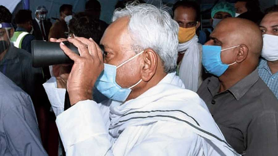 Bihar chief minister Nitish Kumar inspects through binoculars  the increased water levels of Ganga in Patna on Tuesday