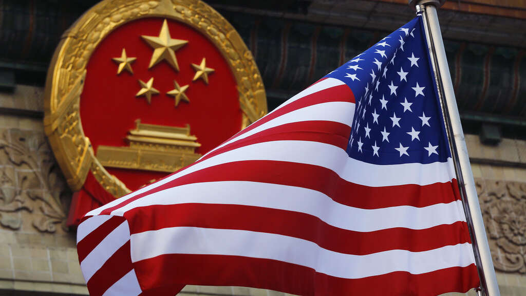 In this Nov. 9, 2017, file photo, an American flag is flown next to the Chinese national emblem during a welcome ceremony for visiting U.S. President Donald Trump outside the Great Hall of the People in Beijing. U.S. and Chinese trade envoys discussed strengthening coordination of their government's economic policies during a phone meeting, the Ministry of Commerce announced.