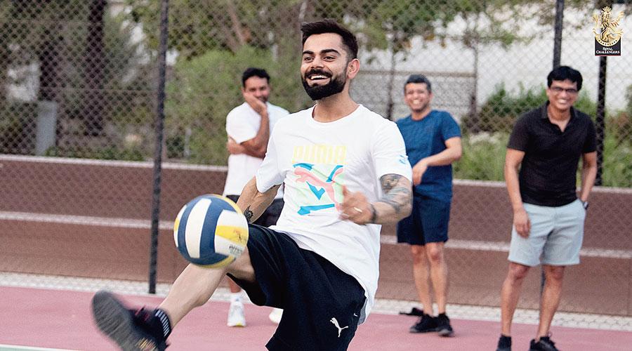 Royal Challengers Bangalore captain Virat Kohli kicks a ball around in Dubai.