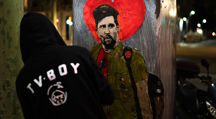 Artist TVBOY glues a painting depicting Lionel Messi dressed like Che Guevara named