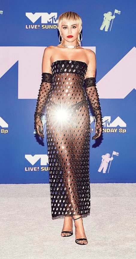 1. When it's the VMAs, it's hard keeping Miley Cyrus away from the red carpet and well, of course, the stage. The Wrecking Ball singer who has had innumerable moments at the award ceremony over the years, turned up looking smoking hot in a sheer dress by Mugler. The black bandeau and matchy panty had a shimmery sheer covering that was adorned with mirrors. The look was complemented by her signature red puckers, large disco hoops, diamond bracelets and her fave sticking-out-tongue pose.