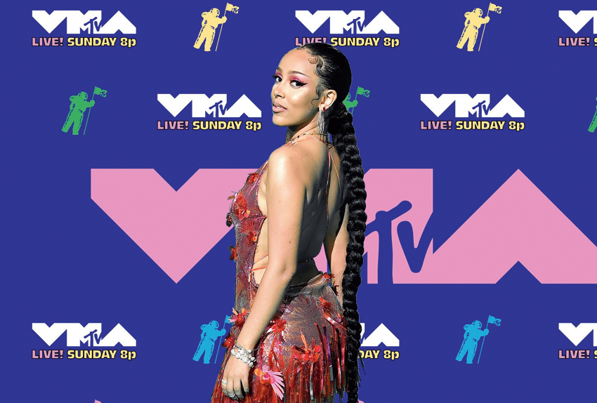 3. Doja Cat kept the hotness metre soaring high in a backless and plunging neckline metallic red dress that had floral detailing and fringes. Big hoops, red eyedo and a long braided hairstyle summed her red-carpet look.