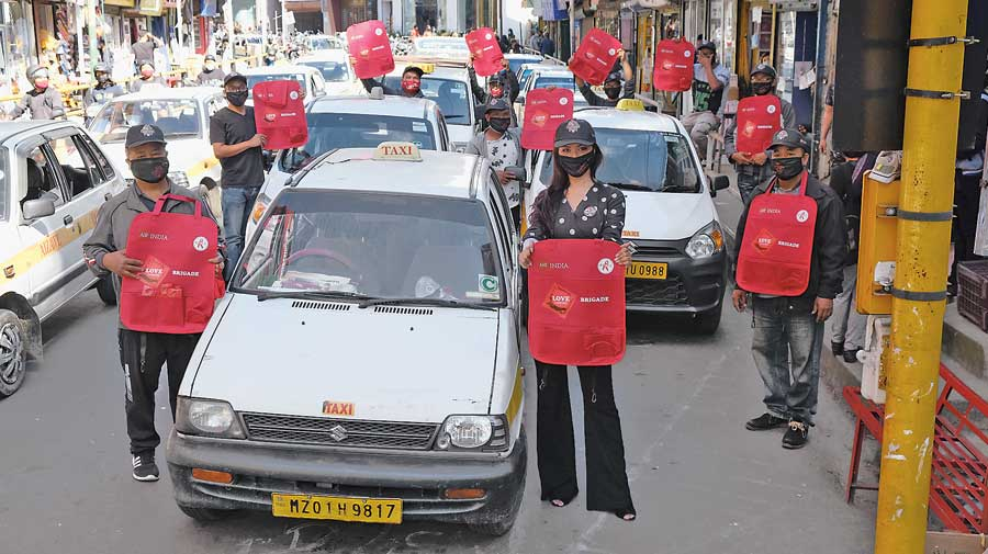 Volunteers distribute red jackets with condoms to taxi drivers.