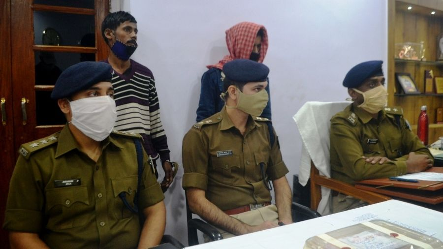 Senior Superintendent of Police, M Tamil Vanan (sitting extreme right), with the arrested duo standing behind him at the police station in Jamshedpur on Wednesday.