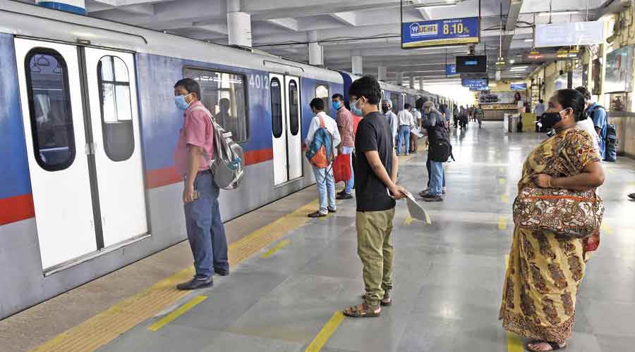 Passengers maintain distance while waiting to board a train at Dum Dum Metro station