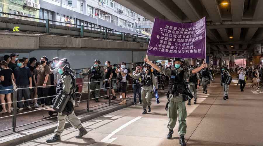 A file picture of a police officer holds up a sign that warns protesters about actions that violate the new national security law at Causeway Bay, a shopping district in Hong Kong, July 1, 2020