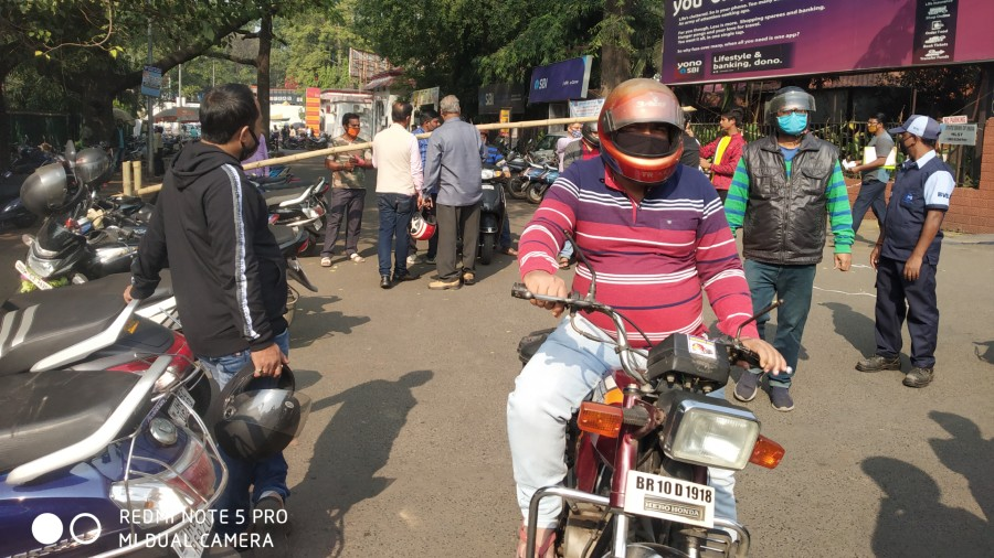 Vehicle riders handing over parking slip at the exit of a parking lot near SBI main branch in Bistupur on Thursday.