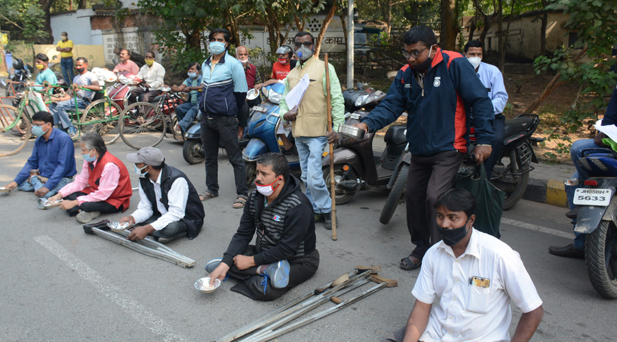 Disabled persons stage protest with begging bowl on the Subarnarekha Link Road in Sakchi, Jamshedpur on Thursday.