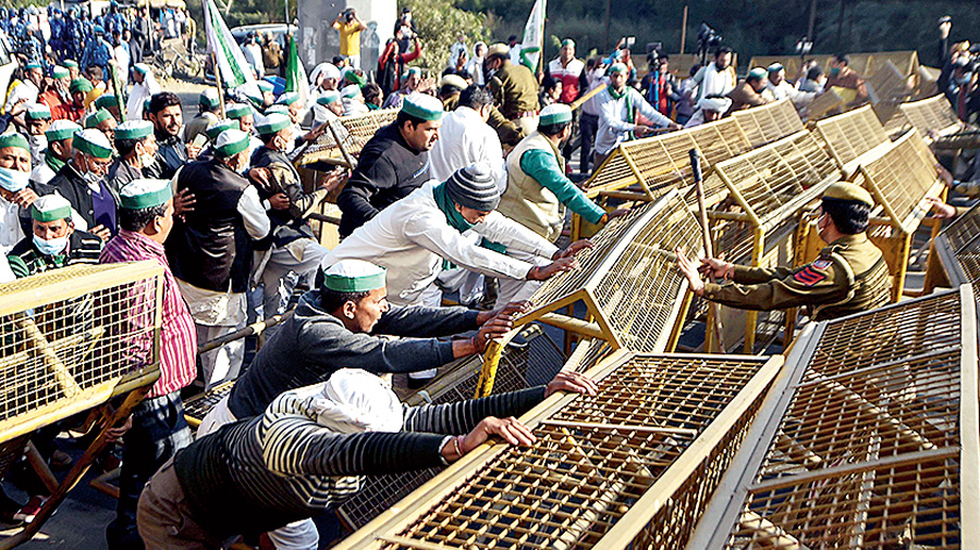 Bharatiya Kisan Union (BKU) members attempt to cross barricades at Ghazipur border as they march during 'Delhi Chalo' protest against the new farm laws, in New Delhi, Saturday, Nov. 28, 2020.