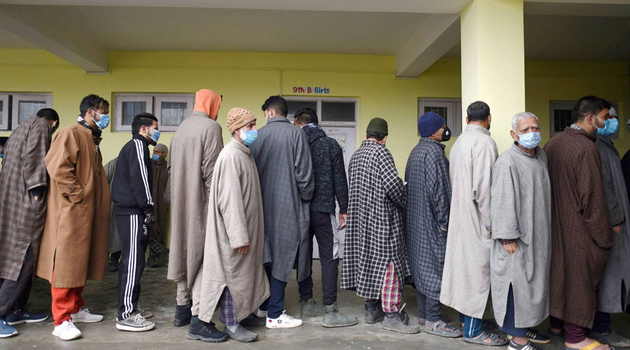 Voters stand in a queue to cast their votes during the third phase of DDC elections, at a polling station in Ganderbal area of Central Kashmir on Friday, December 4, 2020.