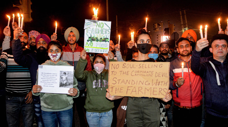 People take part in a candle march in support of the farmers, protesting against the Centers new farm laws, in Jalandhar on Friday, December 4, 2020.