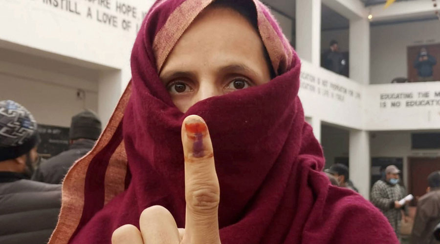 A woman shows her ink-marked finger after casting her vote during the third phase of DDC elections, at a polling station in Ganderbal area of Central Kashmir on Friday, December 4, 2020.
