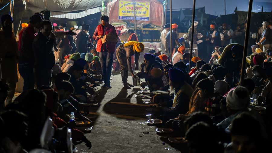 Members of various farmer organisations serve langar to fellow farmers at the Singhu border in New Delhi on Saturday.