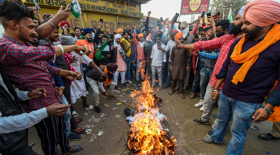 Farmers burn an effigy during their ongoing Delhi Chalo agitation against the new farm laws, at Singhu border in New Delhi on Sunday.
