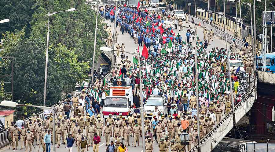 Police keep vigil as Karnataka farmers participate in a protest rally in Bangalore on Wednesday.