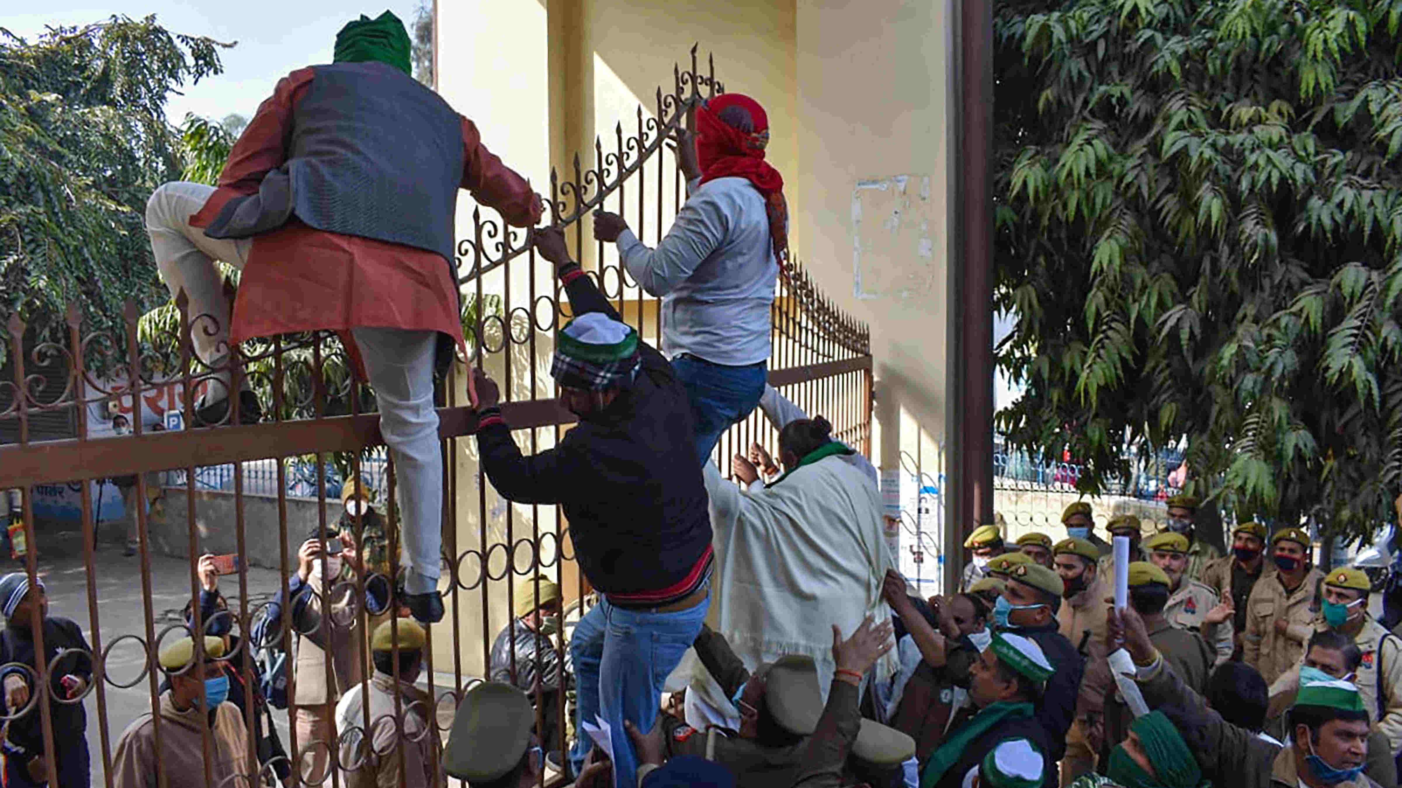 Bharatiya Kisan Union (BKU) workers climb on a gate during their protest, in Bulandshahr, Monday, Dec. 14, 2020.