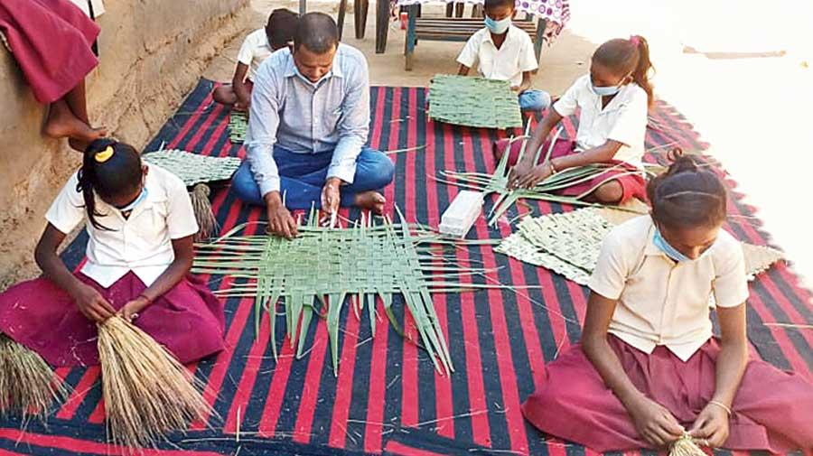 Students make mats and brooms along with headmaster Sapan Kumar at Dumarthar village in Jharkhand's Dumka.