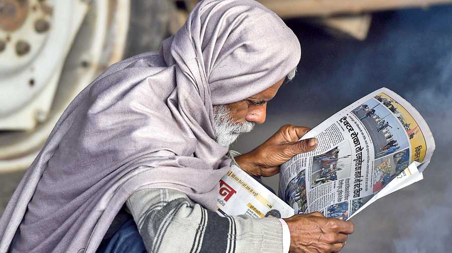 A farmer reads a newspaper during the sit-in at the Ghazipur border on Wednesday.