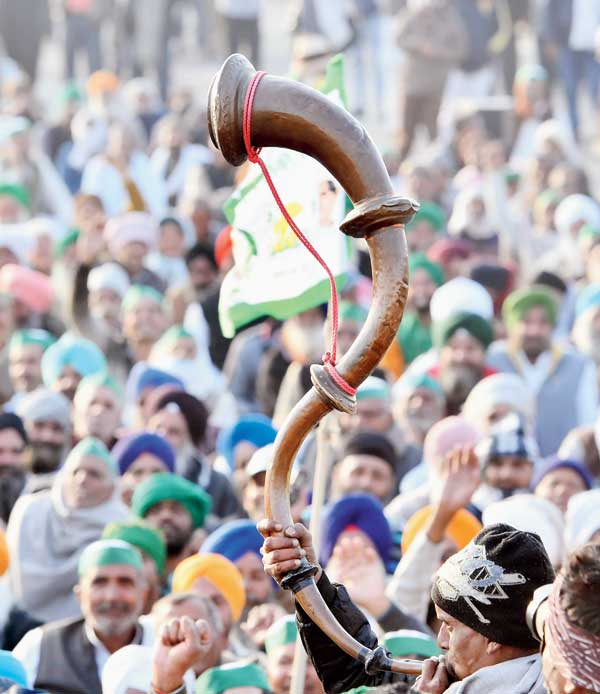A farmer plays a bugle during the protest at the Ghazipur border on Thursday.