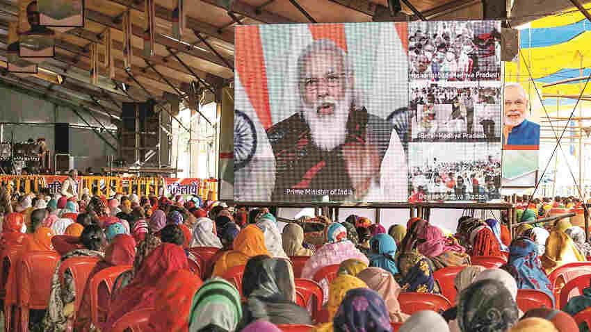 Farmers watch the live telecast of Prime Minister Narendra Modi's speech on a screen during 'Kisan Mahasammelan', in Raisen, Friday, Dec. 18, 2020
