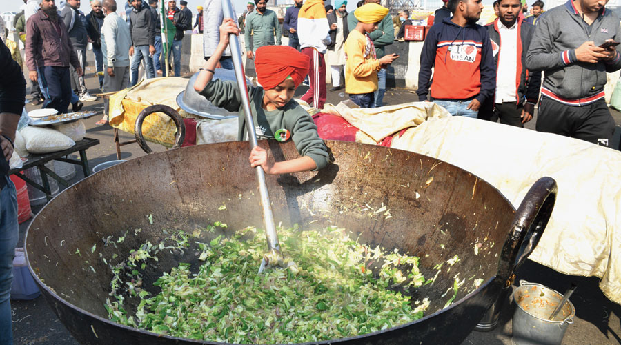 A boy lends a hand at preparing the langar at the farmers' protest site  at Delhi's Ghazipur border.