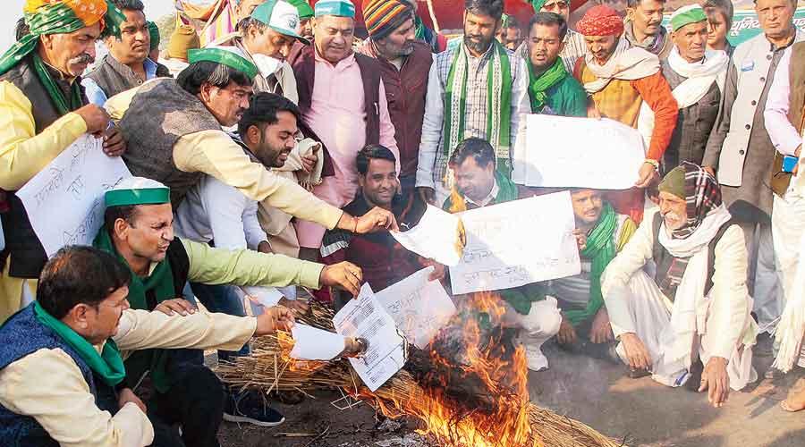 Farmers burn copies of the three farm bills at the  Delhi-Noida border on Tuesday.