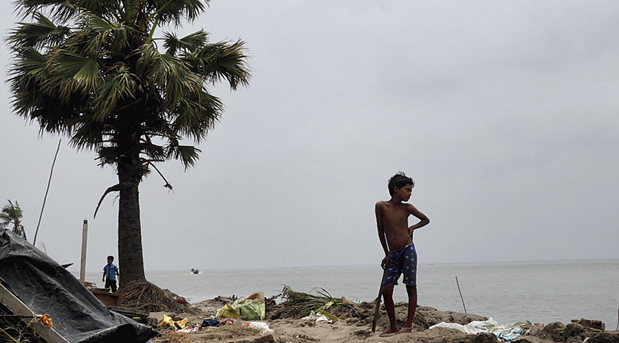 This May 22, 2020 photo shows a boy looking at the damage caused by Cyclone Amphan in Deulbari village, in the Sundarbans.