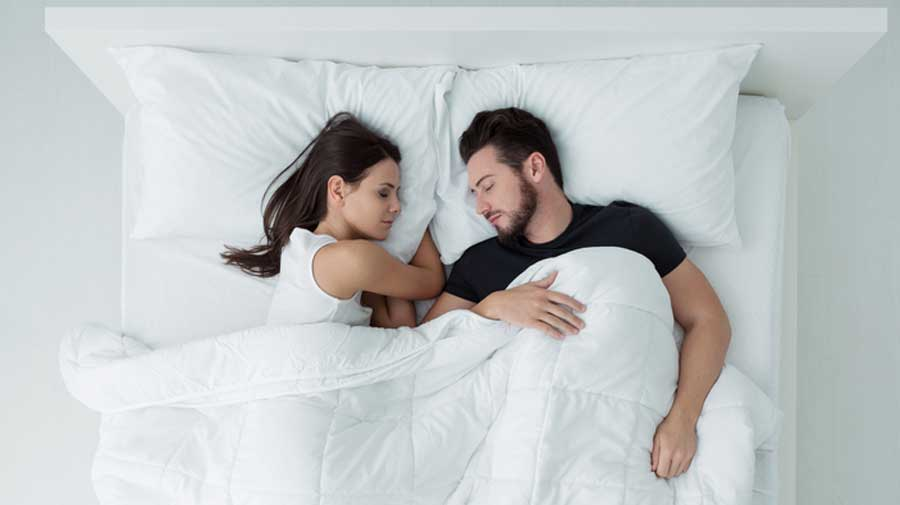 Relaxing and safe environments encourage REM sleep so that may be a reason for happy couples getting more of it.