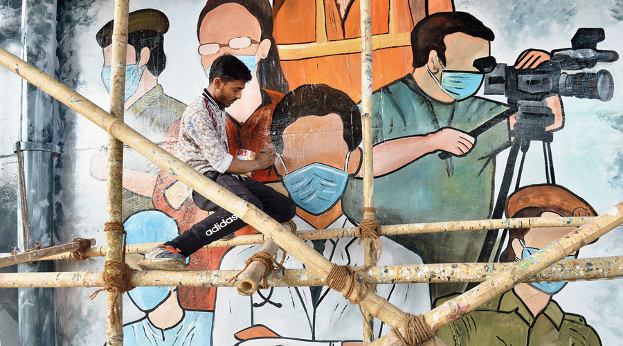 An artist paints a mural to honour Covid-19 warriors  in Noida on Wednesday.