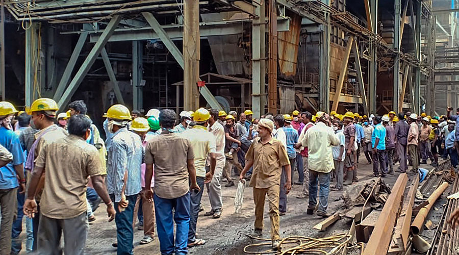 Workers stand outside Neyveli Lignite Corporation power plant following an explosion in Cuddalore district on Wednesday.