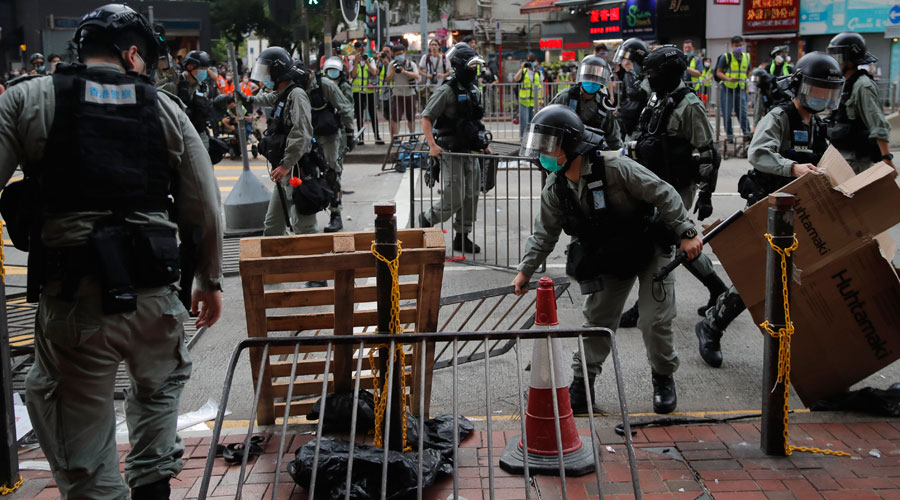 Riot police clear blockages on a road after pushing back protesters in Hong Kong