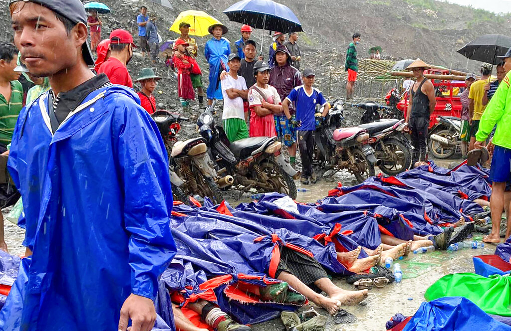 People gather near the bodies of victims of a landslide near a jade mining area in Hpakant, Myanmar, on  Thursday, July 2, 2020