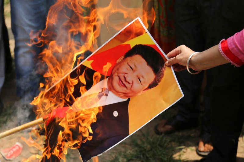 A Bharatiya Janata Party activist burns a photograph of Chinese President Xi Jinping during a protest in Jammu, India, Wednesday, July.1, 2020. Indian TikTok users awoke Tuesday to a notice from the popular short-video app saying their data would be transferred to an Irish subsidiary, a response to India's ban on dozens of Chinese apps amid a military standoff between the two countries. The quick workaround showed the ban was largely symbolic since the apps can't be automatically erased from devices where they are already downloaded, and is a response to a border clash with China where 20 Indian soldiers died earlier this month.