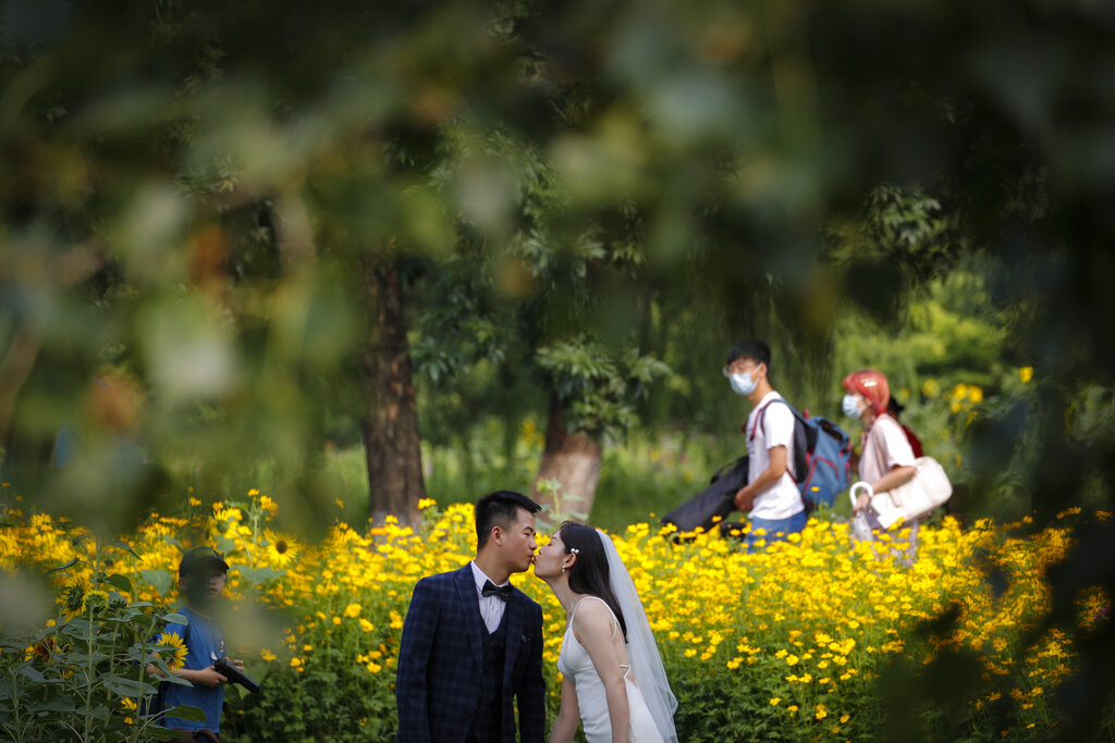 People wearing face masks to help curb the spread of the coronavirus pass by a newly weds kissing as they posing for wedding photos at the Olympic Forest Park in Beijing, Thursday, July 2, 2020. China reported three new cases of coronavirus, including just one case of local transmission in the capital Beijing, appearing to put the country where the virus was first detected late last year on course to eradicating it domestically, at least temporarily.