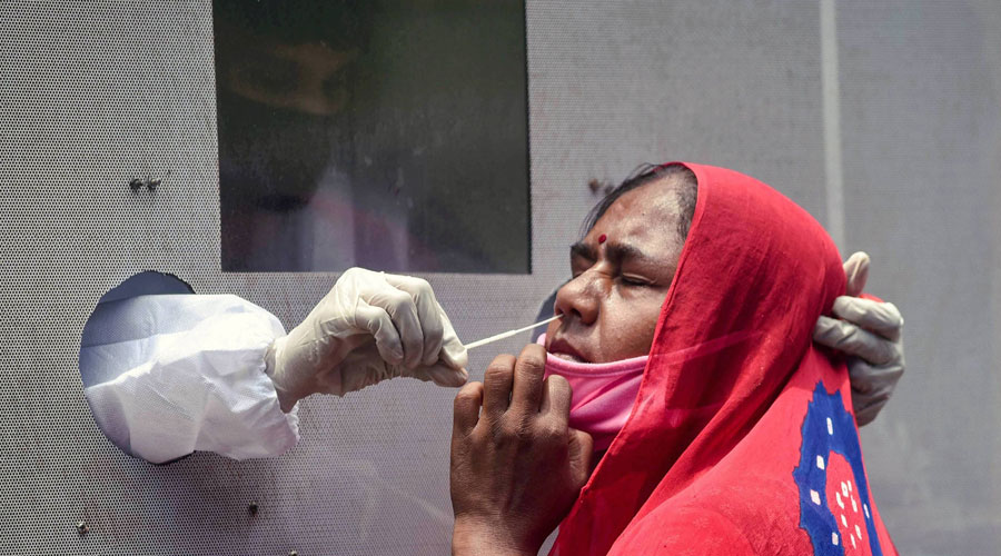 A healthcare worker collects a sample of a woman for the COVID-19 test from a swab collection bus, in Vijayawada, Thursday, July 2, 2020.