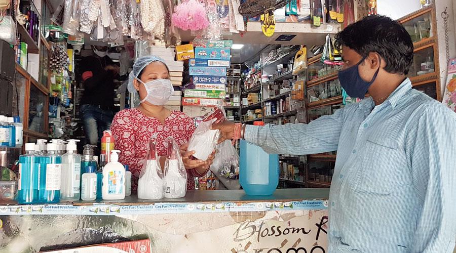 A customer checks out sanitiser spray bottles at Petals, Baisakhi.
