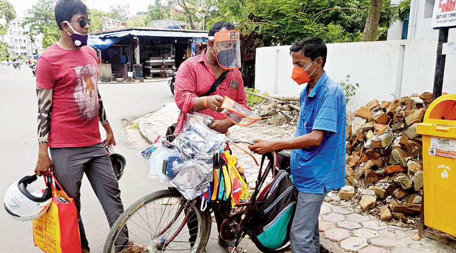 A cycle-borne salesman shows face guards to a potential customer opposite Baisakhi Abasan.