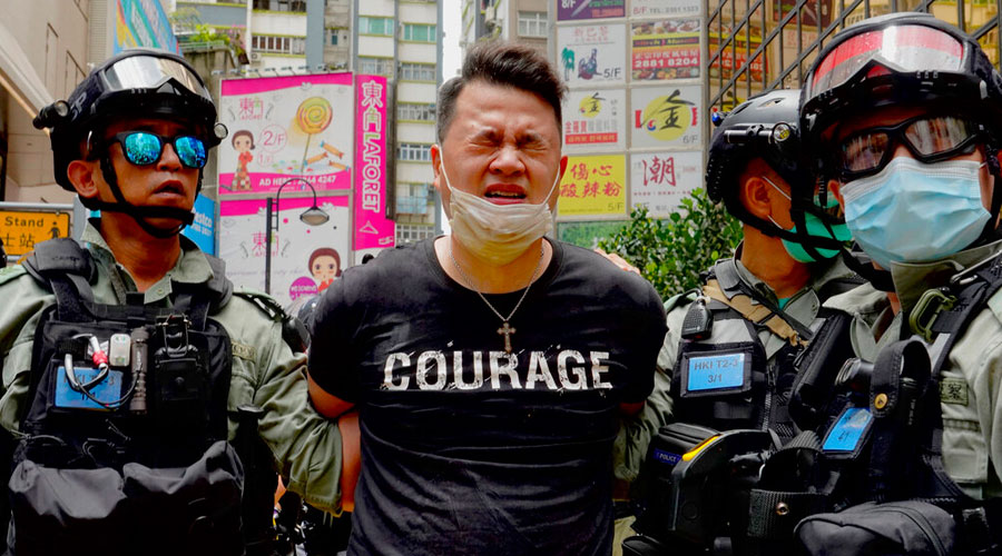 Police detain a protester after being sprayed with pepper spray during a protest in the annual handover march in Hong Kong on Wednesday