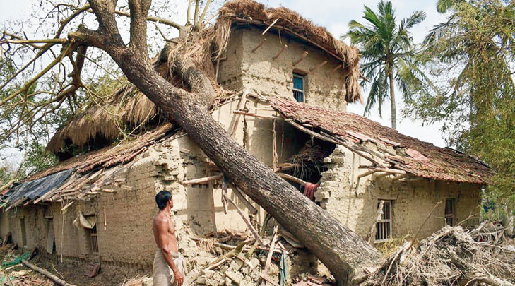 A resident inspects his house damaged during Cyclone Amphan