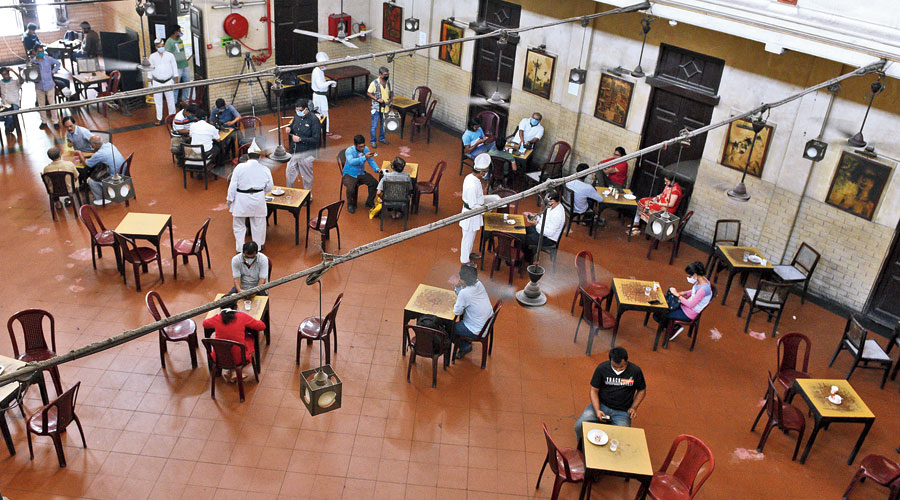 Coffee with care: Customers sit at tables kept at a distance from each other as a precaution against Covid-19 at Coffee House, on College Street, which reopened after the lockdown on Thursday.