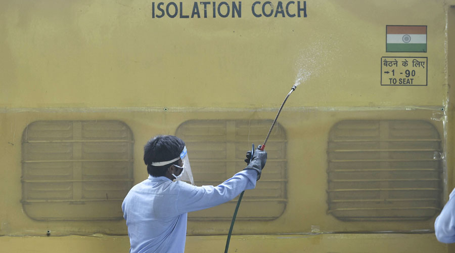 A worker sanitises a railway coach that has been converted into an isolation centre for Covid-19 patients in New Delhi