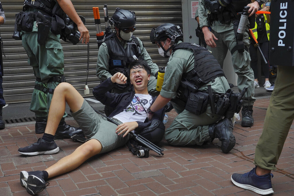 A reporter falls down after being sprayed with pepper spray by police during a protest in Causeway Bay during the annual handover march in Hong Kong, Wednesday, July. 1, 2020.