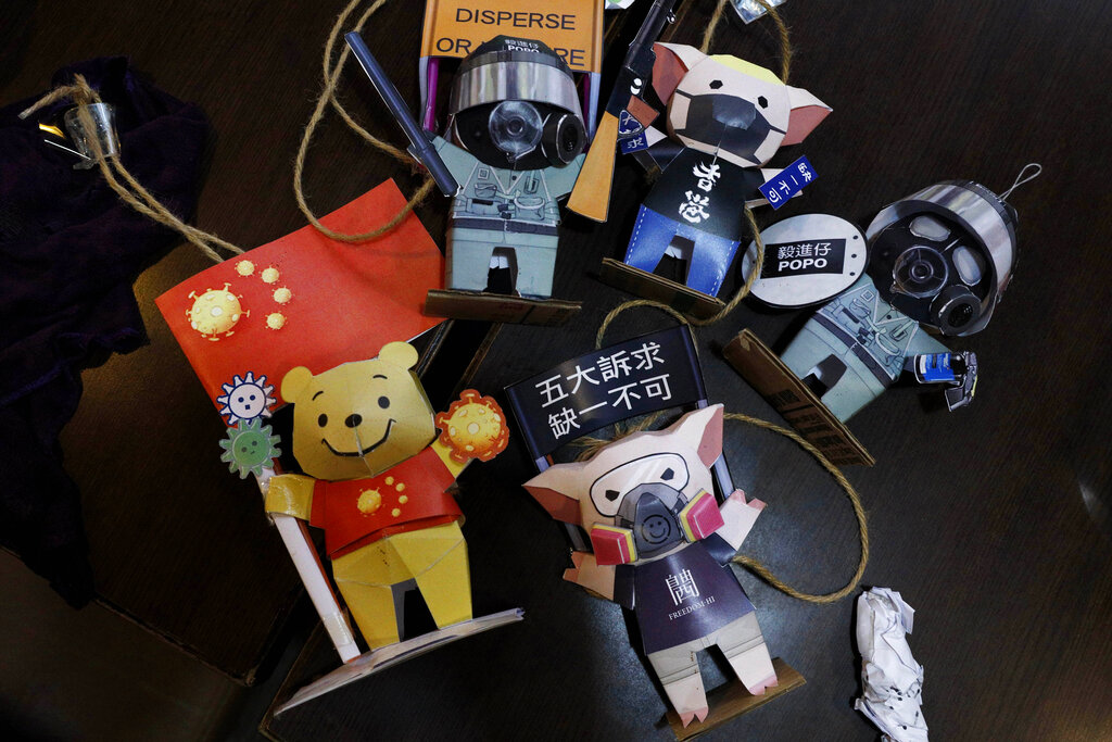 Paper figures of police officers, protesters and Winnie the Pooh, with messages in support of the pro-democracy movement are removed at a restaurant in Hong Kong, Thursday, July 2, 2020.
