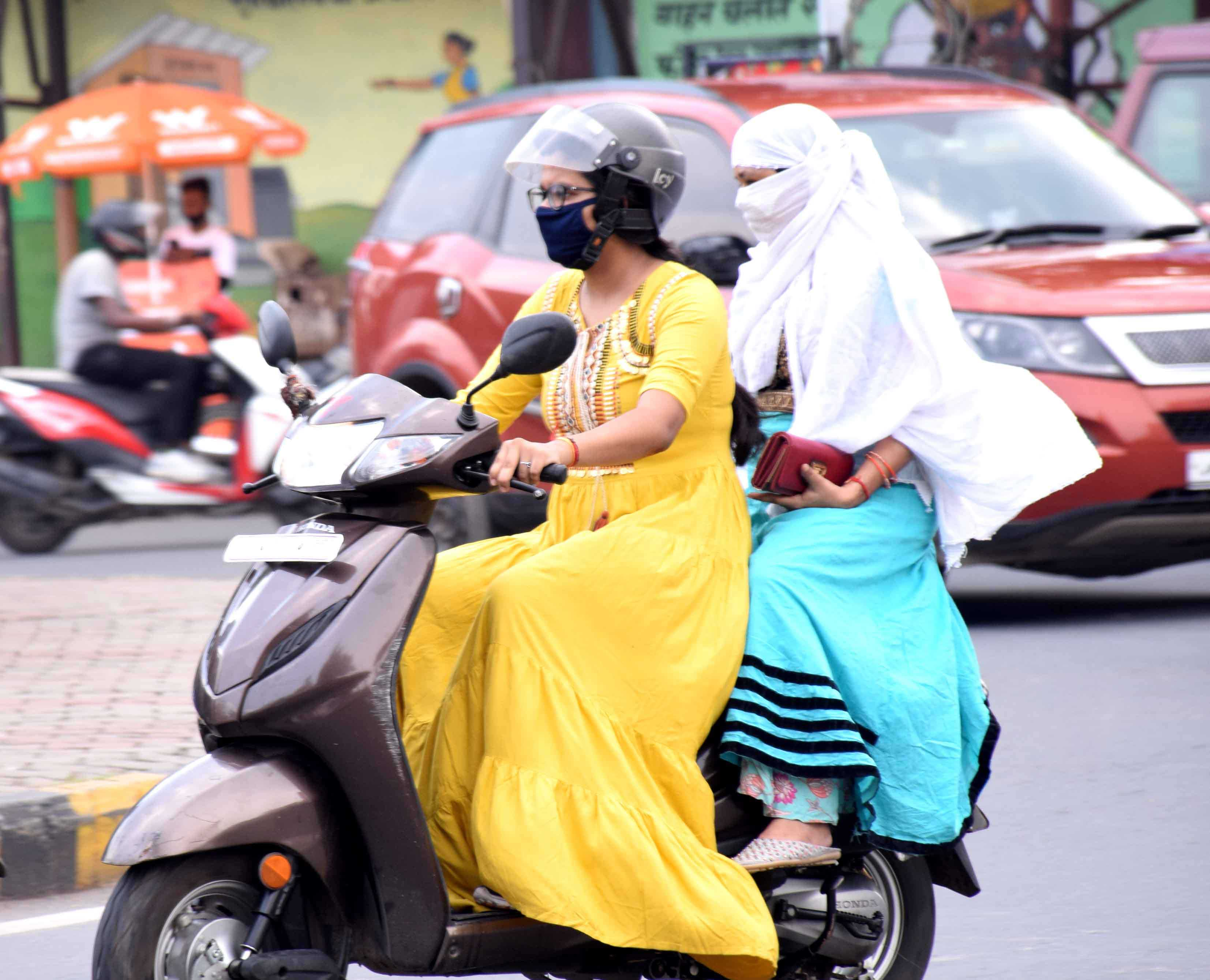 Two women ride through a road in Sakchi on a sultry afternoon on Friday