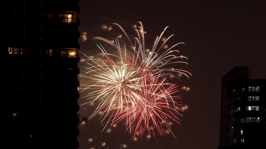 Fourth of July fireworks display lights up the sky beyond an apartment building, Friday, July 3, 2020, in downtown Kansas City, Missouri